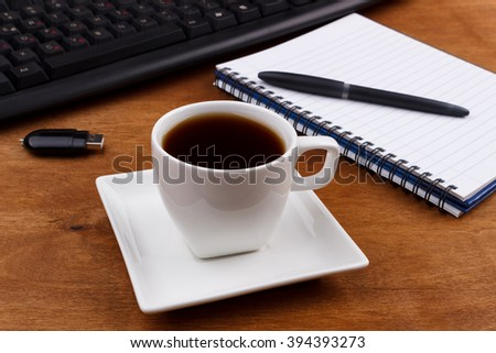 Overhead of office table with computer keyboard,mouse,memory stick,notepad,coffee mug and book on wooden desk