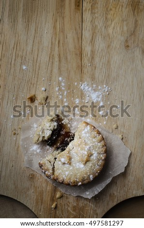 Overhead shot of a partially eaten Christmas mince pie with crumbling pastry and dusting of icing sugar, on an old wooden chopping board.