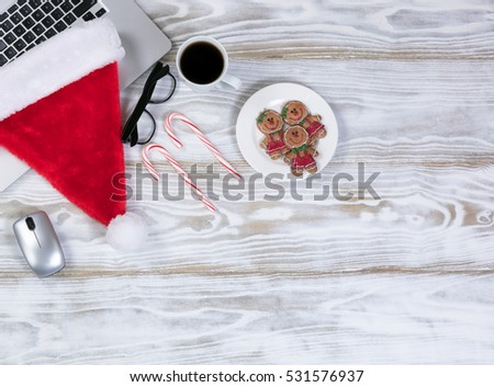 Overhead view of a holiday office workplace desk with cookies and coffee and a Santa cap on laptop keyboard.