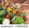 Overhead view of an array of different fresh country herbs and vegetables on a wooden kitchen surface ready to be used as ingredients in vegetarian cuisine - stock photo
