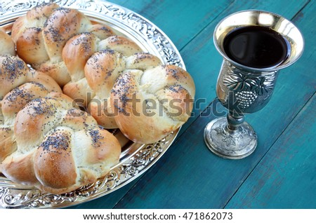 Overhead view of Shabbat eve table with uncovered challah bread and Kiddush wine cup.