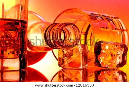 Overturned whiskey bottle and glasses in front of multi colored abstract background.