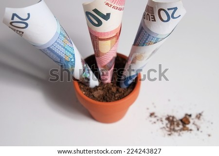 Overview of three Euro banknotes planted in a clay pot growing out. Isolated objects with debris on the table surface