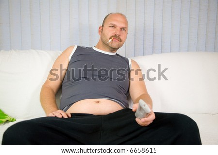 Overweight man sitting on the couch with cigarette in his mouth