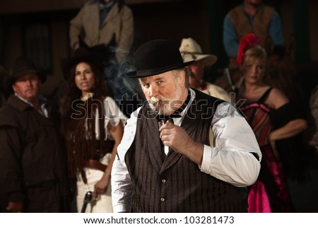 Overweight 1800s style man in front of bandit gang