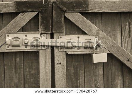 Padlock and a locking bar on an old wooden door (in sepia, vintage style)