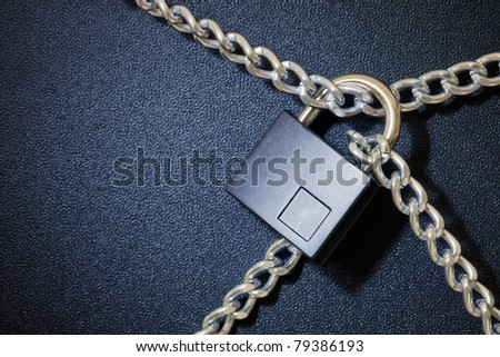Padlock and chain on dark background