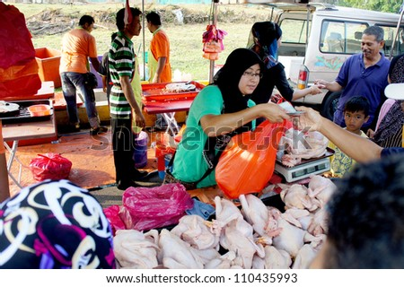PAHANG, MALAYSIA-AUG 18: Unidentified chicken meat seller attends to a customer at Pasar Ramadan Kuantan on August 18, 2012 in Pahang, Malaysia. Muslims around the world celebrate Aidilfitri tomorrow