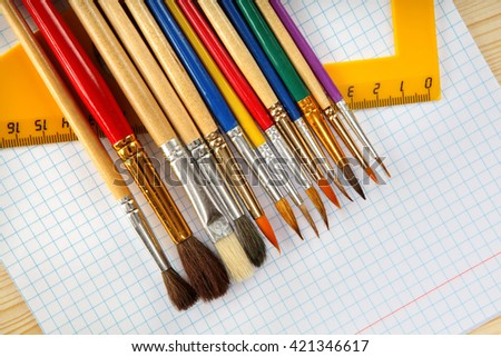 Paint brushes, ruler and checkered paper on wooden background