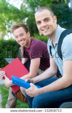 pair of happy young male students on campus