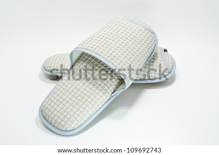Pair of house slippers with reflection on white background