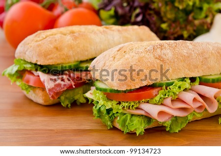 Pair of sandwiches filled with salami, chicken breast and lettuce