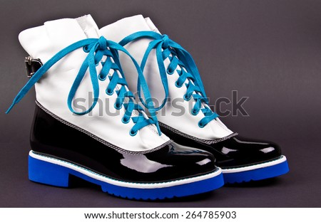 pair of stylish women's black and white shoes with blue laces and soles, on a gray background