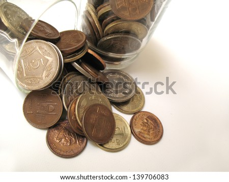 Pakistani coins in jar and on the floor