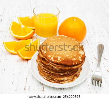 pancakes with orange and orange juice on a wooden table