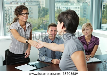 Panel of business people sitting at table in meeting room conducting job interview greeting female applicant.
