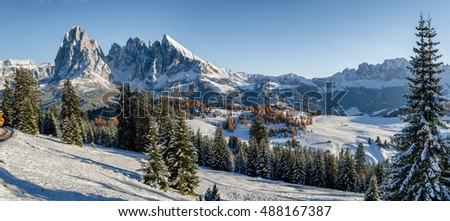 Panorama image of the Seiser Alm or Alpe di Siusi, a high altitude alpine meadow in the Dolomites with Langkofel and Plattkofel mountains under a layer of snow in winter in South Tyrol, Italy.