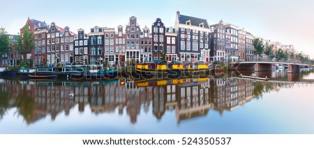 Panorama of Amsterdam canal Singel with typical dutch houses, bridge and houseboats during morning blue hour, Holland, Netherlands.