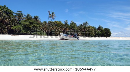Panorama of pristine island shore with tropical vegetation and a boat landed on the beach, Caribbean sea, Panama