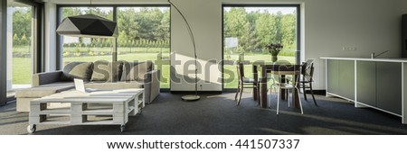 Panorama of spacious interior with sofa, small table, dining set, decorative floor lamp and big windows