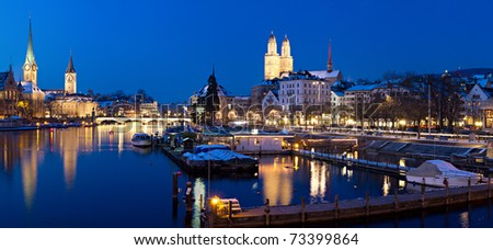 Panorama: Zurich, swiss financial center seen from river Limmat at night with historic city center and it's churches reflecting in the stream