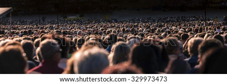 Panoramic photo of large crowd of people. Slow shutter speed motion blur.