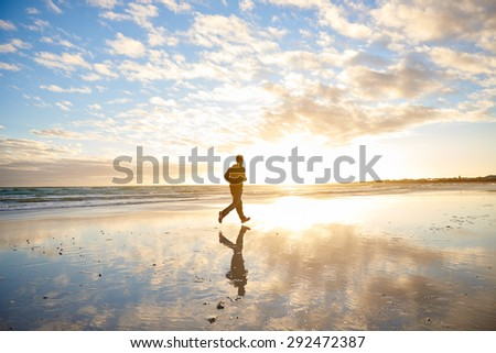 Panoramic shot of a young man running along the shoreline at the beach with dramatic clouds overhead and early morning sun flare
