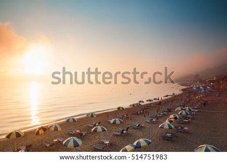 Panoramic view of beach in Agios Gordios of Corfu, Greece, at sunset from above, distant coastline covered with mist