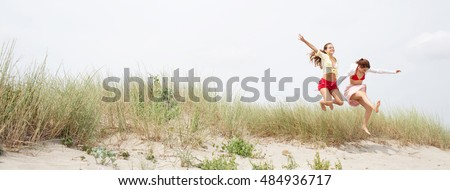 Panoramic view of sisters girls joyfully smiling, holding hands jumping together in sand dunes holiday beach destination, travel lifestyle. Young women having fun, happy expressions. Active play.