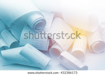 Paper cash register receipts in a lose pile close up with soft focus