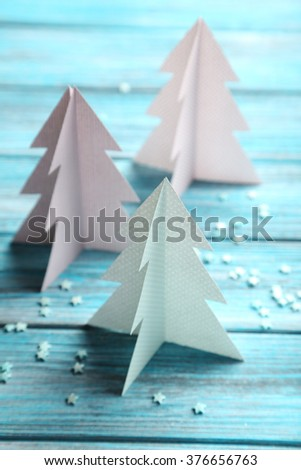 Paper Christmas trees on blue wooden table