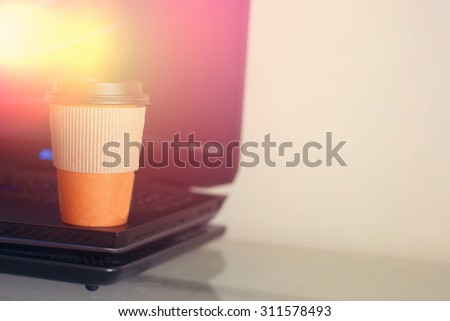 Paper cup of coffee and laptop