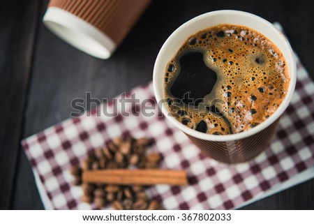 paper cup of hot coffee on wooden table