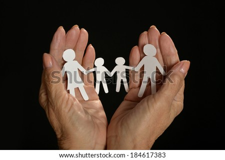 Paper family in hands isolated on black background
