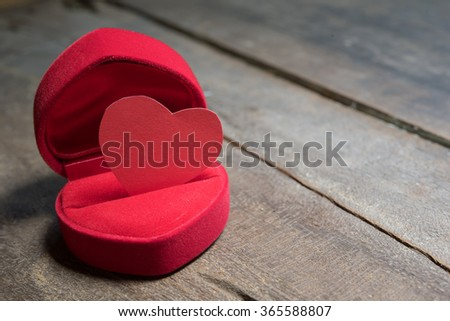 paper red heart shape in box on wood floor