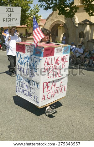 Parade participants carrying signs about peace make their way down main street during a Fourth of July parade in Ojai, CA