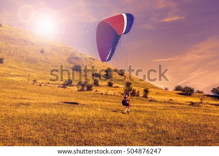 Paraglider over the green valley, sunset sky