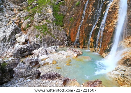 Parallel water streams pouring into small pond on Lasties valley, Sella massif, Dolomite Alps, Italy