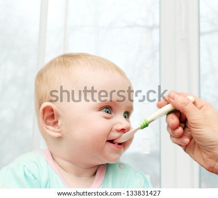 Parent feeding Hungry Baby in home interior
