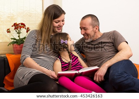 Parents and child having fun reading together