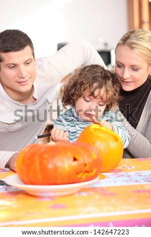 Parents and daughter in the kitchen preparing pumpkin