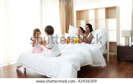Parents having breakfast and children playing on the bed