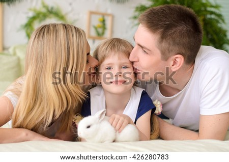 parents kiss his beautiful daughter, who is holding the white rabbit