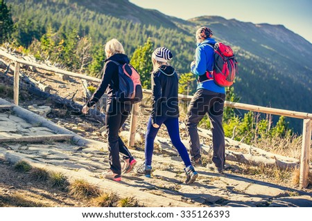 Parents with daughter hikers trekking in mountains.