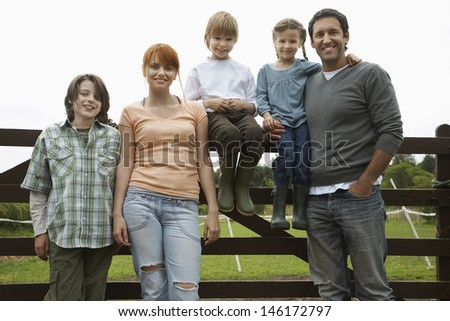 Parents with three children standing against fence in the field