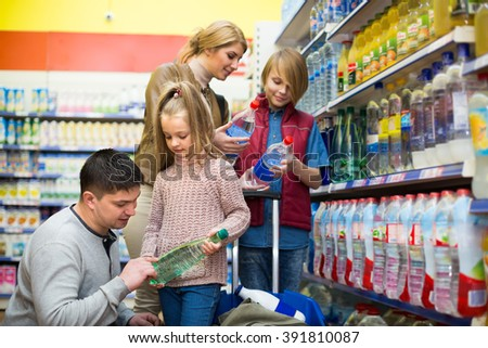 Parents with two children purchasing bottle of sparkling water in supermarket. Selective focus