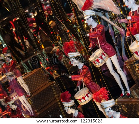 PARIS - DECEMBER 9: Christmas  decoration in the windows of Galeries Lafayette department store on December 9, 2012 in Paris, France. Colorful marionettes drummers attract adults and children.