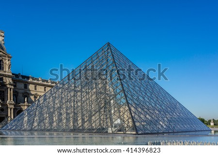 PARIS, FRANCE - JULY 16, 2012: View of pyramid and fountain at courtyard of Louvre Museum. Louvre Museum is one of the largest and most visited museums worldwide.