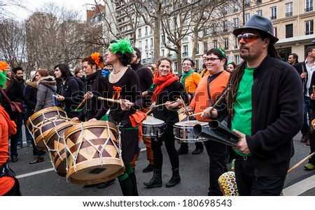 PARIS, FRANCE - MARCH 2, 2014: Unidentified participants green orange costume at the Carnival in Paris. Colorful Carnaval de Paris is annual event, which history starts from the sixteenth century.