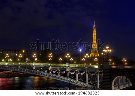 PARIS, FRANCE - MAY 9, 2014:  Eiffel Tower (Tour Eiffel) and Pont Alexandre III at night illumination. The Eiffel tower is the most famous and visited monument of France.